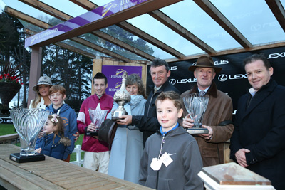 LEOPARDSTOWN MON 28 DECEMBER 2015  PICTURE: CAROLINE NORRIS   JENNY HOWES PRESENTING THE TROPHY FOR THE LEXUS STEEPLECHASE WON BY DON POLI TO EDDIE O'LEARY, WITH JED O'LEARY AND HIS FAMILY, BRIAN COOPER AND WILLIE MULLINS ALSO IN PHOTOGRAPH
